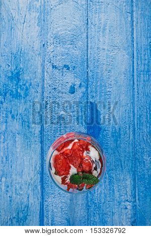 Red sorbet with fresh plum and cream served in glass bowl over blue wooden background