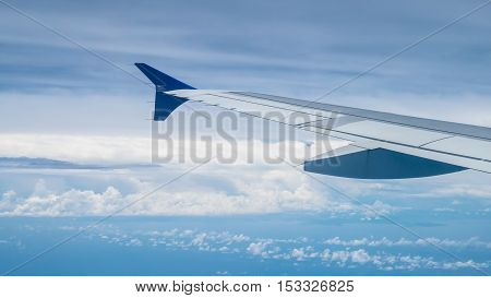 The airplane wing on the beautiful cloudy and sky.