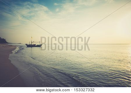 Beautiful sunset and beach with fishing boat -Dark tone color
