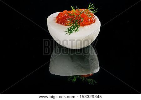 Hard-boiled egg with salted salmon roe filling isolated over black reflective background