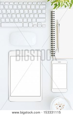 phone and tablet blank screen on white table format vertical top view