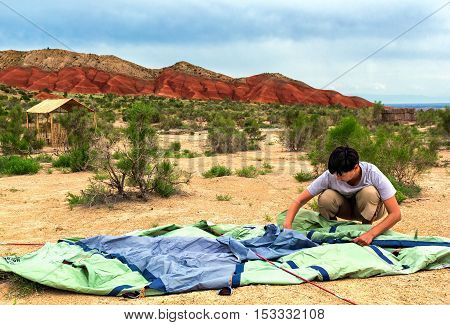 Woman collects tent on a background of mountains