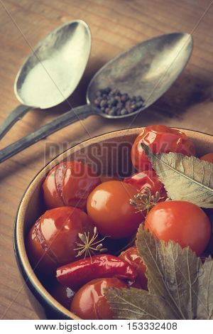 Canned tomatoes in a ceramic plate and two old spoons with salt and pepper on a wooden board