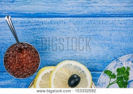 Salted salmon roe in the little steel bowl and lemon slices over sky-blue wood plank background. Closeup. Flat lay