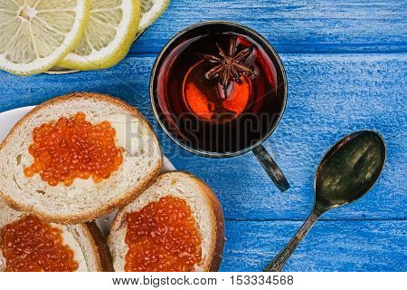 Toasts with salted salmon roe and lemon slices over sky-blue wood plank background. Closeup. Flat lay