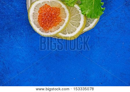 Salted salmon roe on lemon slices over spotty blue background. Closeup. Flat lay
