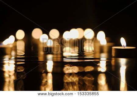Defocused golden candlelight with reflection in darkness