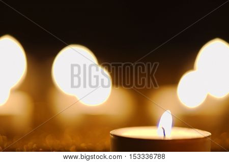 Close-up of a burning candle against golden candlelight background