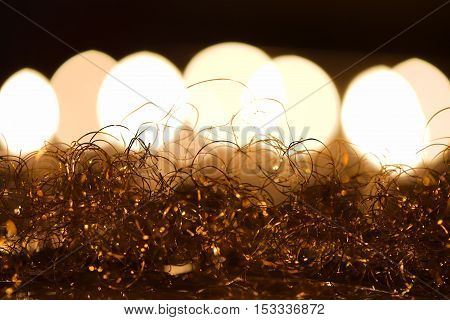 Christmas decoration: golden angel hair against candlelight bokeh background