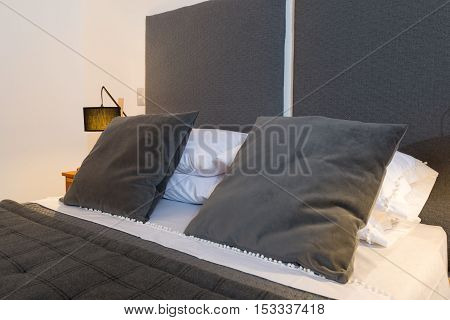 Bed headboard with cushions and pillows detail