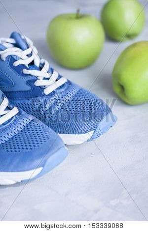 Sport Shoes And Apples On Gray Concrete Background