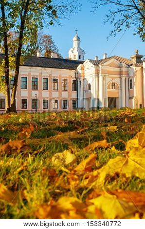 Veliky Novgorod Kremlin park with Clock Tower of St Sophia Cathedral and fallen maple autumn leaves on the foreground in Novgorod Russia. Selective focus at the clock tower.