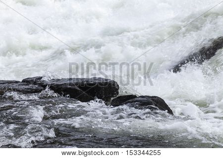 Cascades of water in the big river. Rocks and cliffs break the speed.