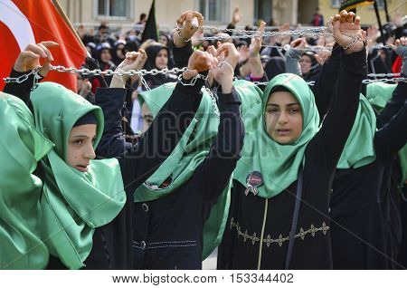 Istanbul Turkey - October 11 2016: Shiite Muslim women hold up their chained hands as they mourn during an Ashura procession. Turkish Shia Muslims mourning for Imam Hussain. Caferis take part in a mourning procession marking the day of Ashura in Istanbul'