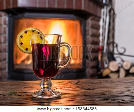 Hot mulled wine with orange slice, cloves and cinnamon stick. Fireplace with warm fire on the background.
