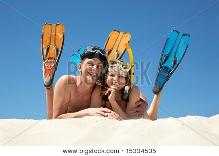 Portrait of cheerful couple in aqualungs looking at camera with smiles