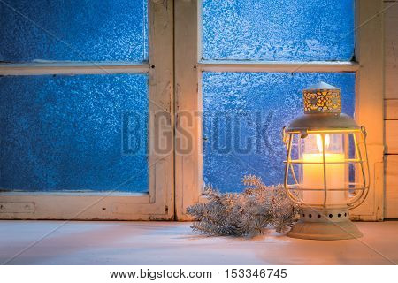 Frosted window with candle for Christmas on old white table