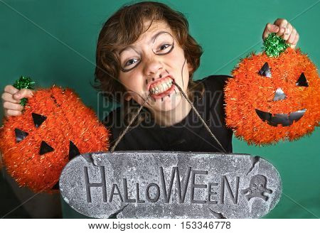 portrait of teen boy with halloween inscription make up and pumpkins close up portrait