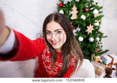 Young Woman Taking Selfie Photo Near Decorated Christmas Tree