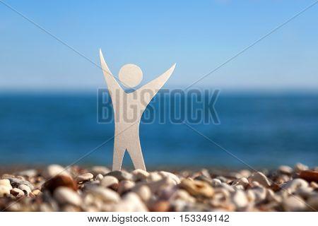 White paper male figure on a gravel beach
