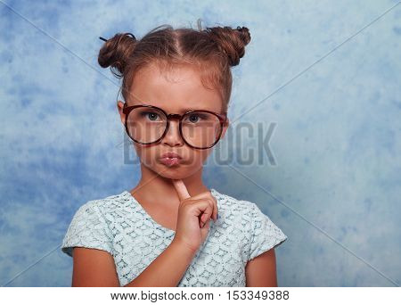 Serious Angry Kid Girl With Modern Hair Style In Fashion Glasses Looking With Finger Under Face On B
