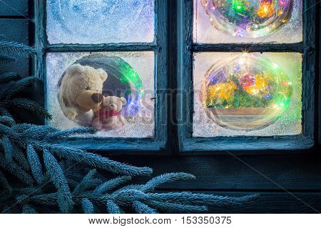 Teddy Bear And Light On Tree For Christmas In Frozen Window