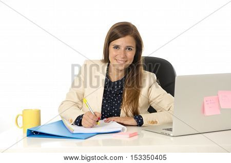corporate portrait of young attractive businesswoman on her 30s sitting at office chair working at laptop computer desk taking notes writing on pad smiling happy