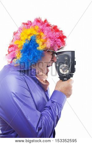 Man with rainbow wig using old movie camera isolated on white background
