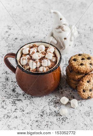 Hot chocolate chocolate chip cookies and christmas ornament Santa Claus on a light background