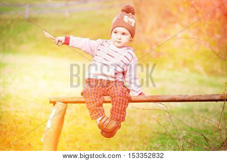 A little boy is sitting on a Park bench under a tree.