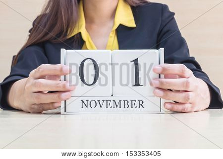 Closeup white wooden calendar with black 1 november word in blurred working woman hand on wood desk in office room selective focus at the calendar