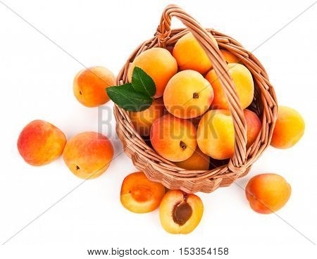 Fresh apricot with green leaf in wicker basket still life of fruits. Isolated on white background and copyspace top view
