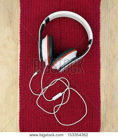 Headphones on a red knitted scarf (on wooden background.) The plug disconnected. / Silence. Privacy. Loneliness. Relax. / Christmas tunes. Walk with music. Fashionable accessories. Top view. Modern life.