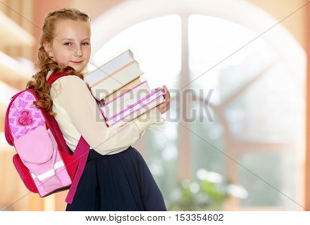Beautiful small girl schoolgirl in black skirt and white blouse goes to school. Behind the girl a big red schoolbag , holding her stack of books. Close-up.In a room with a large semi-circular window.