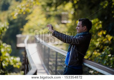 male traveler with smart phone taking a photo of beautiful landscape.