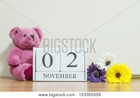 Closeup surface white wooden calendar with black 2 november word on brown wood desk and cream color wallpaper in room textured background with copy space selective focus at the calendar
