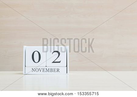 Closeup surface white wooden calendar with black 2 november word on blurred brown wood desk and wood wall textured background with copy space selective focus at the calendar