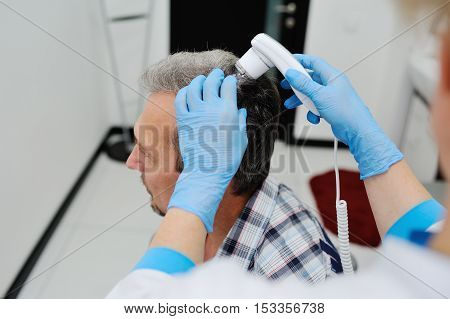 baldness. diagnostics hair and scalp. Trihoskopiya. Doctor examine patient male hair a special apparatus.