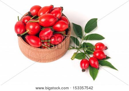 fresh rosehip berries in a wooden bowl isolated on white background.