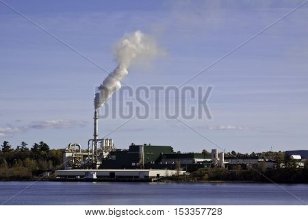 Miramichi Catham NB October 15 2016 -- Wide view of large industrial building with smoke stack spewing a cloud of billowous smoke on a bright sunny day in October. Shot is taken from the Miramichi side looking across the Miramichi River at Chatham.