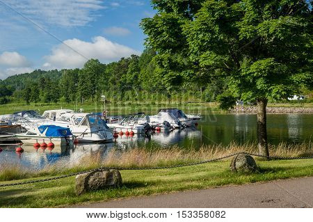 Shore of lake in Norway, near the Horten town. Fishing boats moored at camping site.