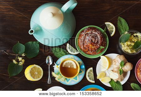 Cup With Green Tea, Lemon And Baked Goods On The Wooden Background