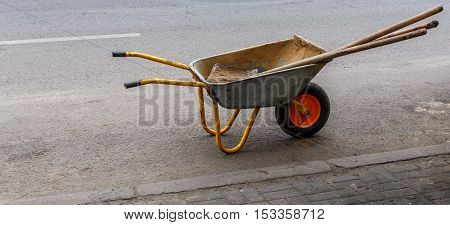 Construction wheelbarrow with sand and shovels in it