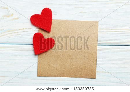 Red Hearts And Sheet Of Blank Paper On A Blue Wooden Table