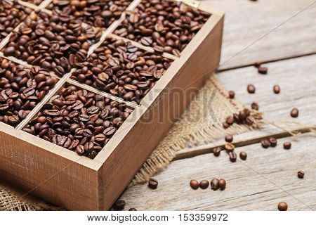 Roasted Coffee Beans In Wooden Basket On Grey Table