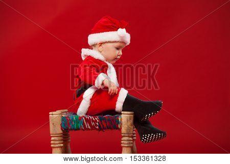cute kid in Santa Claus clothes. sitting on a chair.