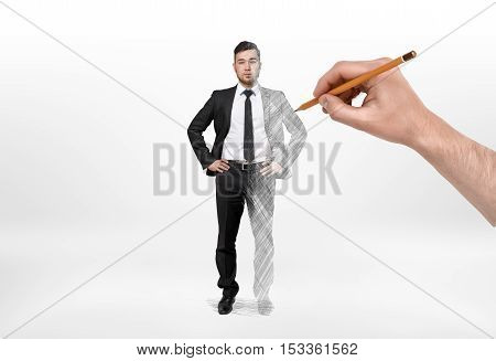 Businessman having the left half a real man and the right half a picture that is drawing with a pencil held in someone's hand. Creating a successful man. Starting a business from nothing. Image making.