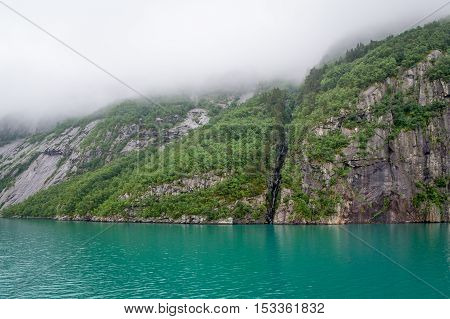 Scenic rocky cliffs and turquise water of norwegian fjords. Deep fog in the sky. Lysefjord, Norway.