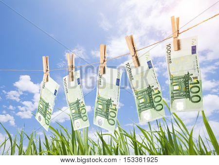 100 Euro Banknotes Hanging On Clothesline On Grassland Background.