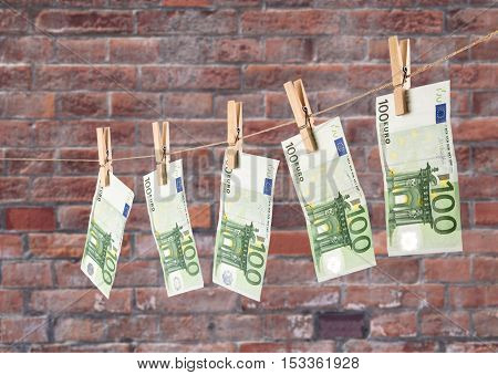 100 Euro Banknotes Hanging On Clothesline On Brick Wall Background.